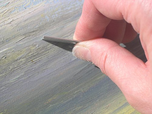 Scraping the old painting with a razor blade